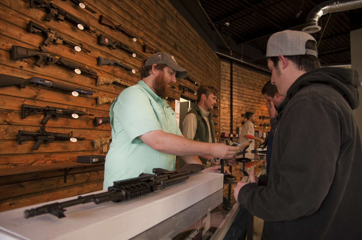 Danny Anderson, S&K Arms assistant manager, helps Preston Zaya Monday, 2-23-15, during the grand opening of the new gun store. Tim Fischer\Reporter-Telegram