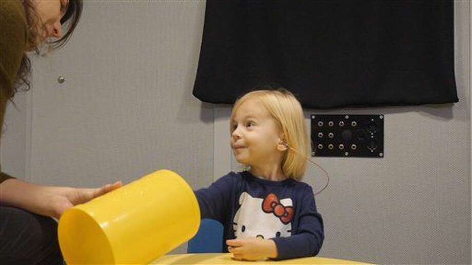 "In this images from video provided by University of North Carolina at Chapel Hill, a toddler participates in a speech perception experiment in a laboratory at the University of North Carolina in Chapel Hill, N.C.. The toddler was conditioned to put a block in the bucket whenever she heard the ""target"" word. From the cacophony of day care to the buzz of TV and electronic toys, noise is more distracting to a child's brain than an adult's, and new research shows it can hinder how youngsters learn. In fact, one of the worst offenders when a tot's trying to listen is other voices babbling in the background, researchers said Saturday at a meeting of the American Association for the Advancement of Science. (Emily Buss/University of North Carolina at Chapel Hill via AP) Photo: Emily Buss"