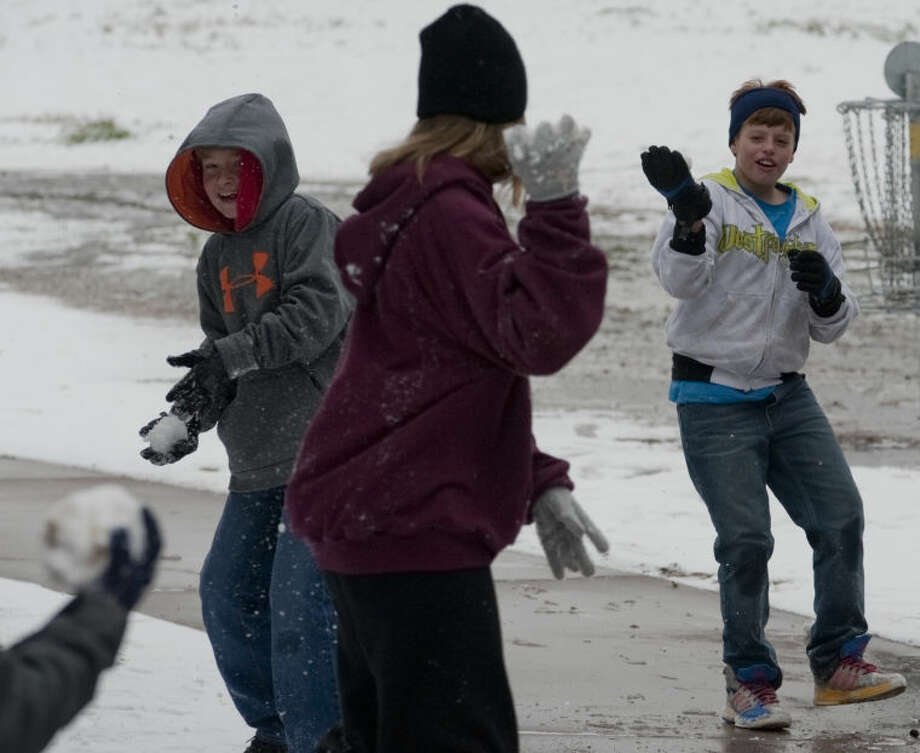 Friends have a snowball fight at Cowden Park Sunday after temperatures dropped and snow fell overnight. Tim Fischer\Reporter-Telegram Photo: Tim Fischer