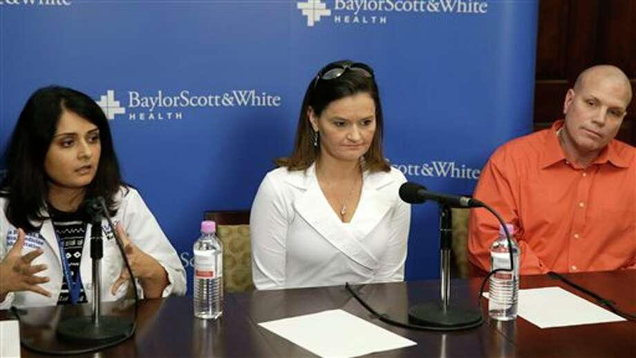 Dr. Seema R. Sikka, left, speaks about the daughter of Holly Wethington, center, and Joe Wethington, right, during a news conference Monday, Feb. 3, 2014, in Dallas. The couple's daughter survived a fall of more than 3,000 feet in a skydiving accident last weekend in Oklahoma. According to her physician, Makenzie Wethington walked with assistance Monday at the Baylor Institute of Rehabilitation in Dallas. (AP Photo/LM Otero) Photo: LM Otero / AP