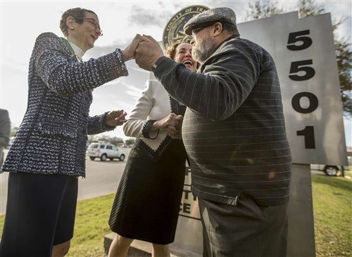 Suzanne Bryant, left, and Sarah Goodfriend hold hands with Rabbi Kerry Baker during their wedding ceremony outside of the Travis County Clerk's office in Austin, Texas on Thursday morning, Feb. 19, 2015. Travis County spokeswoman Ginny Ballard said the marriage occurred Thursday, though it wasn't immediately clear if the license has legal standing. The marriage followed a state District Court order instructing that officials not rely on Texas' unconstitutional prohibitions on same-sex marriage. (AP Photo/Austin American-Statesman, Ricardo B. Brazziell) AUSTIN CHRONICLE OUT, COMMUNITY IMPACT OUT; INTERNET AND TV MUST CREDIT PHOTOGRAPHER AND STATESMAN.COM; MAGS OUT