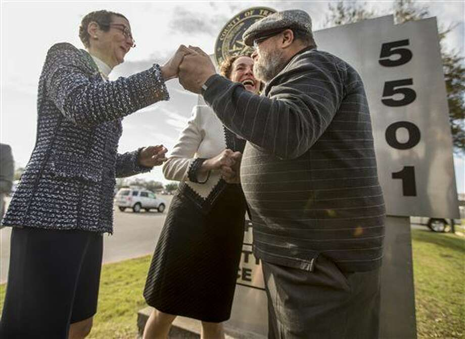 Suzanne Bryant, left, and Sarah Goodfriend hold hands with Rabbi Kerry Baker during their wedding ceremony outside of the Travis County Clerk's office in Austin, Texas on Thursday morning, Feb. 19, 2015. Travis County spokeswoman Ginny Ballard said the marriage occurred Thursday, though it wasn't immediately clear if the license has legal standing. The marriage followed a state District Court order instructing that officials not rely on Texas' unconstitutional prohibitions on same-sex marriage. (AP Photo/Austin American-Statesman, Ricardo B. Brazziell) AUSTIN CHRONICLE OUT, COMMUNITY IMPACT OUT; INTERNET AND TV MUST CREDIT PHOTOGRAPHER AND STATESMAN.COM; MAGS OUT Photo: RICARDO B. BRAZZIELL
