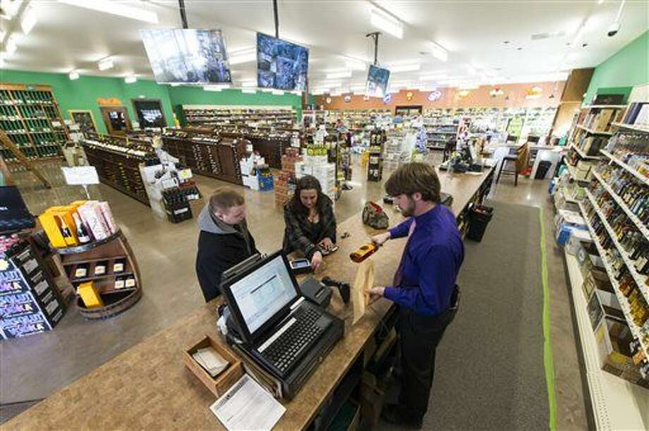Amanda Phillips, center, and Brendon Joyce, left, are checked out by store manager Tyler Pontius at a liquor store in this AP file photo. Photo: Doug McSchooler