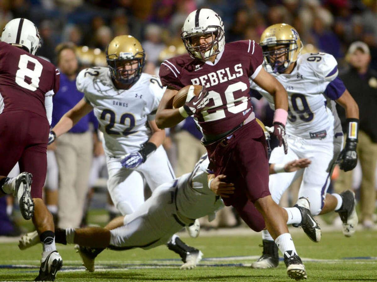Lee's Kaleb Nunez runs the ball while Midland High's Britt Boler tries to tackle him at Grande Communications Stadium. James Durbin/Reporter-Telegram