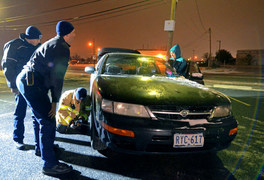 Midland EMS personnel from Station 3 change a flat tire for a stranded motorist near the intersection of Golf Course and N. Big Spring Street Friday, Feb. 27, 2015. James Durbin/Reporter-Telegram Photo: James Durbin
