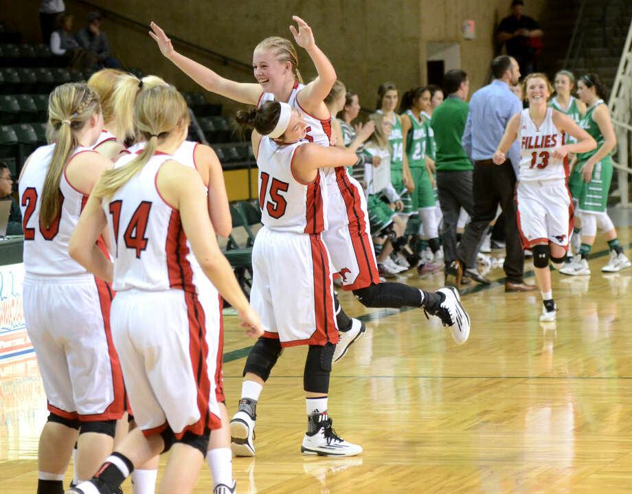 Shallowater's Carlie Breckel (15) and Morgan Bennett (23) embrace as the rest of the team runs in to celebrate a win against Wall in the Region 1-3A semifinal game Saturday, Feb. 28, 2015, at Chaparral Center. James Durbin/Reporter-Telegram Photo: James Durbin