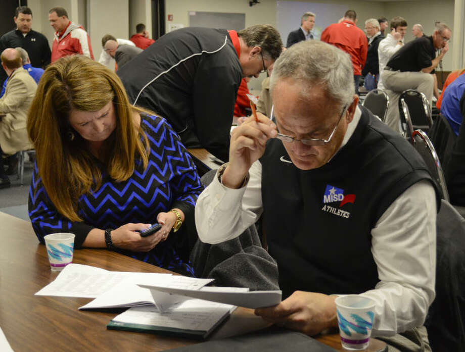 MISD executive director of athletics, Todd Howey, looks over the new UIL realignment paperwork on Feb, 3 as director of athletics, Nancy Surber, makes phone calls to area schools to set up games for the upcoming school year. Tim Fischer\Reporter-Telegram Photo: Tim Fischer