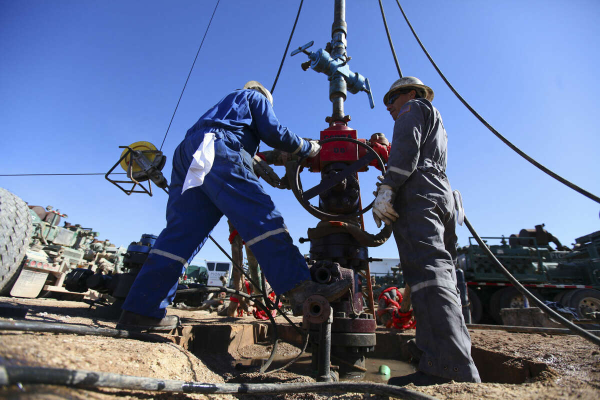 Oil field workers for Pioneer Natural Resources standing at a well that was being fracked on the Giddings Estate, an oil field south of Midland, Texas, Feb. 14, 2012. (Jim Wilson/The New York Times)