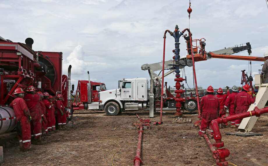 Workers watch as the frac tree is removed from a well at a ranch southwest of Ben Bolt, Texas, on Wednesday, Sept. 11, 2013. The well, located near the Jim Wells and Duvall County line, was drilled to a depth of over one mile. Photo: Jerry Lara