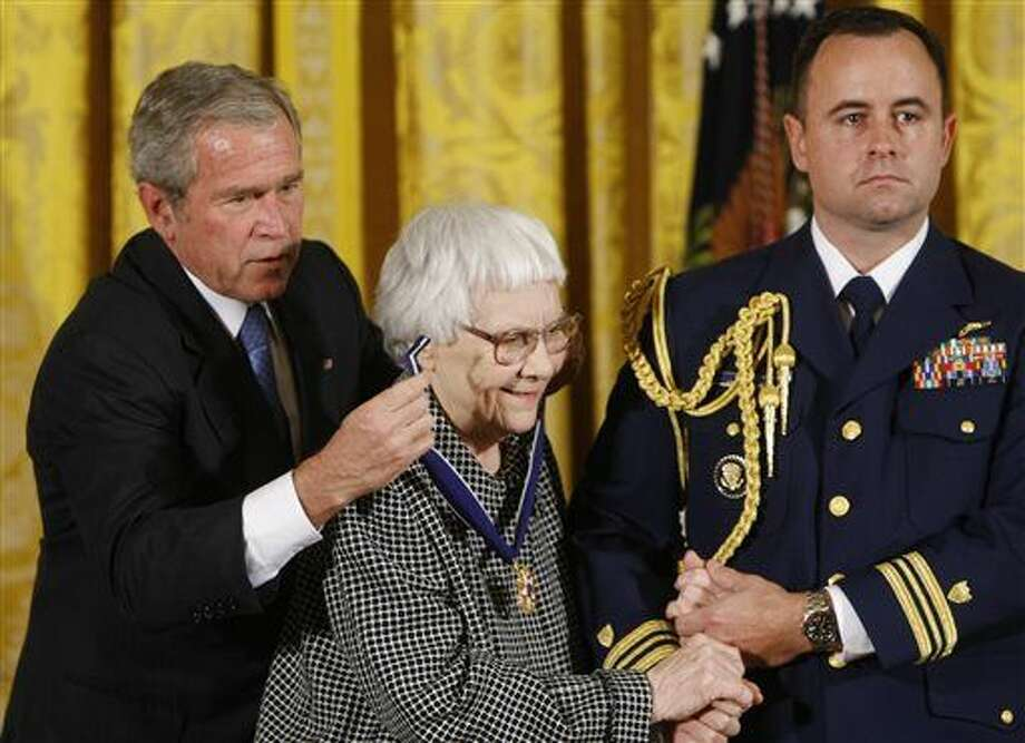 "FILE - In this Nov. 5, 2007 file photo, President Bush, left, presents the Presidential Medal of Freedom to author Harper Lee, center, during a ceremony in the East Room of the White House in Washington. Lee, the elusive author of best-seller ""To Kill a Mockingbird,"" died Friday, Feb. 19, 2016, according to her publisher, Harper Collins. She was 89. (AP Photo/Gerald Herbert, File) Photo: Gerald Herbert"