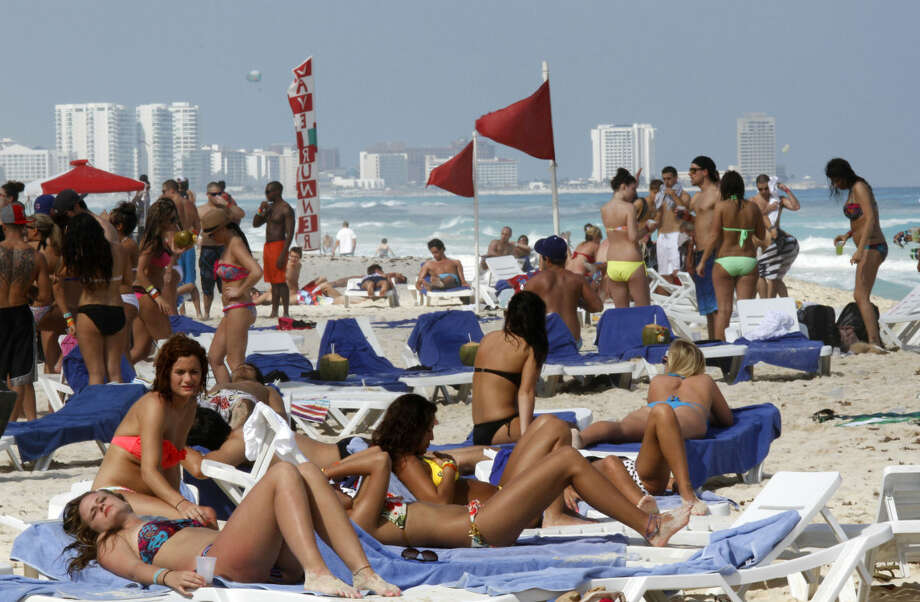 FILE - In this March 10, 2012 file photo, people hang out on the beach during spring break in Cancun, Mexico. The beach resort remains a top destination for American spring-breakers seeking an escape from winter. (AP Photo/Israel Leal, File) Photo: Israel Leal