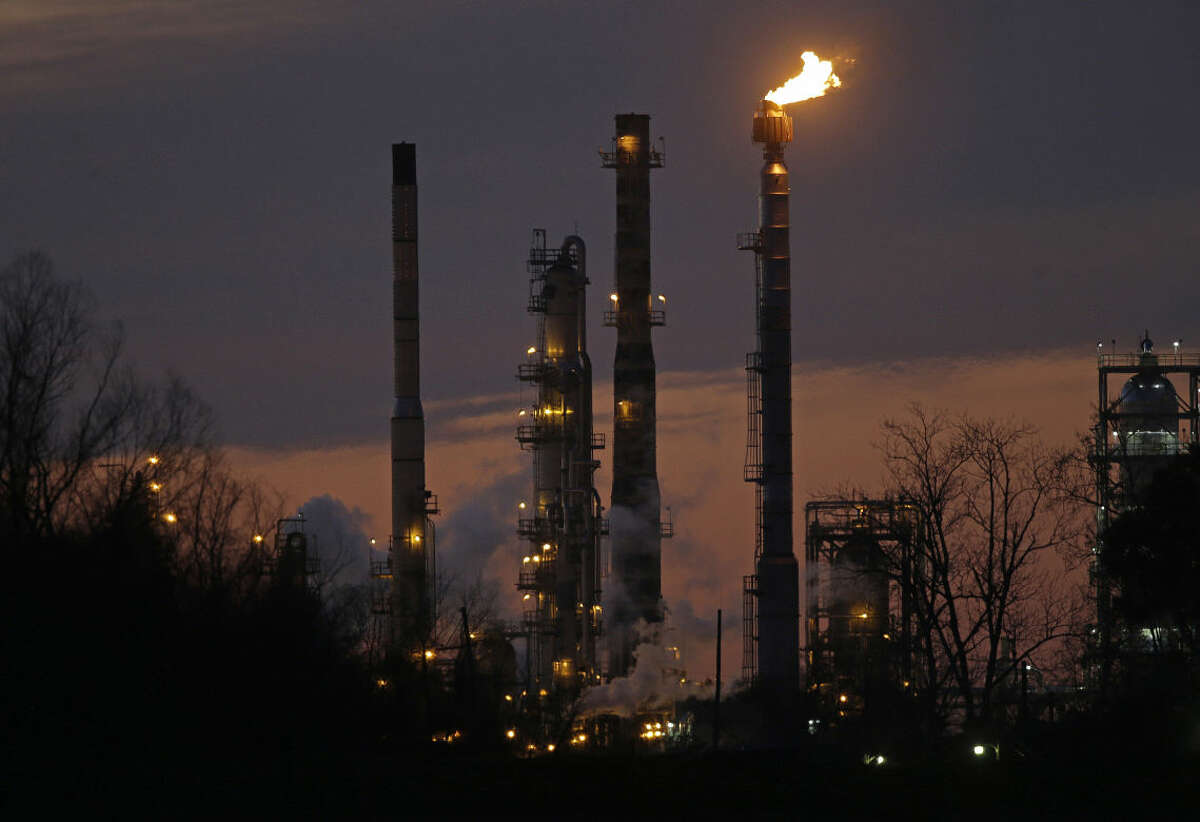 FILE - In this Feb. 13, 2015 file photo, stacks and burn-off from the Exxon Mobil refinery are seen at dusk in St. Bernard Parish, La. The price of U.S. crude oil on Tuesday, Aug. 11, 2015 tumbled to its lowest level in more than six years. (AP Photo/Gerald Herbert, File)