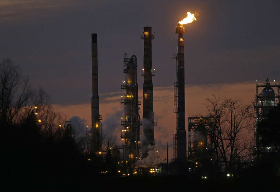 FILE - In this Feb. 13, 2015 file photo, stacks and burn-off from the Exxon Mobil refinery are seen at dusk in St. Bernard Parish, La. The price of U.S. crude oil on Tuesday, Aug. 11, 2015 tumbled to its lowest level in more than six years. (AP Photo/Gerald Herbert, File) Photo: Gerald Herbert