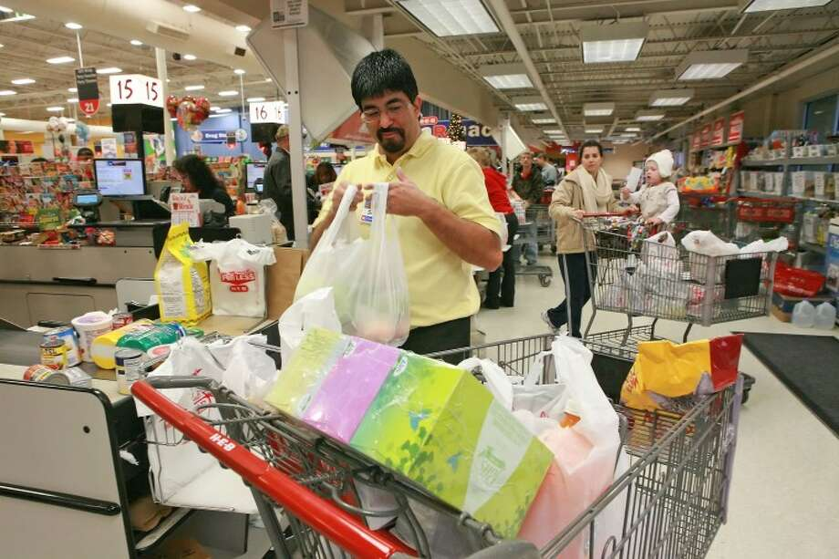 Sid Rodriguez sacks grocries for customers Friday at HEB. HEB will be open Christmas Eve form 6 am to 8 pm and closed Christmas Day. Cindeka Nealy/Reporter-Telegram Photo: Cindeka Nealy