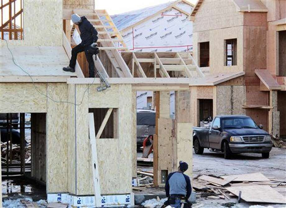 In this Jan. 29, 2016 photo, carpenters work on an apartment complex in Williston, N.D. Gravy days are waning in the oil patch city due to depressed crude prices. And despite a jailbreak-like exodus of oil drillers in the past year, the city is teeming with newcomers from the Congo to Idaho who are opting to stick it out in a still-strong economy instead of starting over somewhere else. (AP Photo/James MacPherson) Photo: James MacPherson