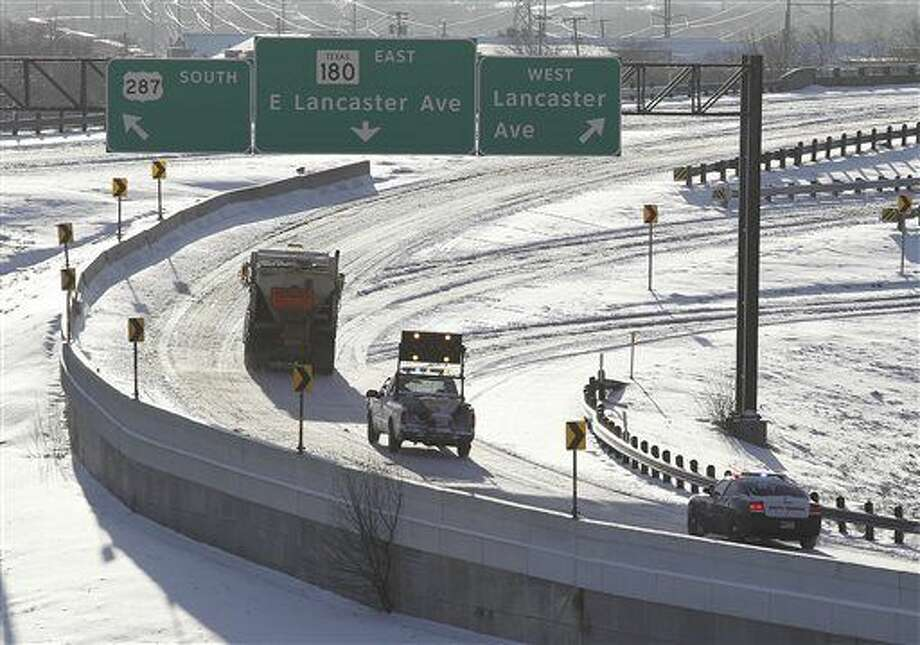 A sand truck and police unit make their way onto Highway 287 as heavy snow that covers roadways in Fort Worth, Texas on Thursday, March 5, 2015. The National Weather Service issued a winter storm warning for the Dallas-Fort Worth area until midday. (AP Photo/The Fort Worth Star-Telegram, Ron T. Ennis) MAGS OUT; (FORT WORTH WEEKLY, 360 WEST); INTERNET OUT Photo: Ron T. Ennis