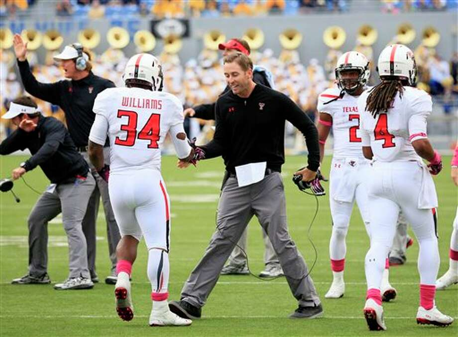 FILE - In this Oct. 19, 2013, file photo, Texas Tech coach Kliff Kingsbury celebrates with Kenny Williams (34) following a touchdown run in the fourth quarter of an NCAA college football game against West Virginia in Morgantown, W.Va. Texas Tech players and coaches say Kingsbury's confidence, drive and energy are behind the No. 10 Red Raiders' success this season. (AP Photo/Christopher Jackson, File) Photo: Chris Jackson / FR170573