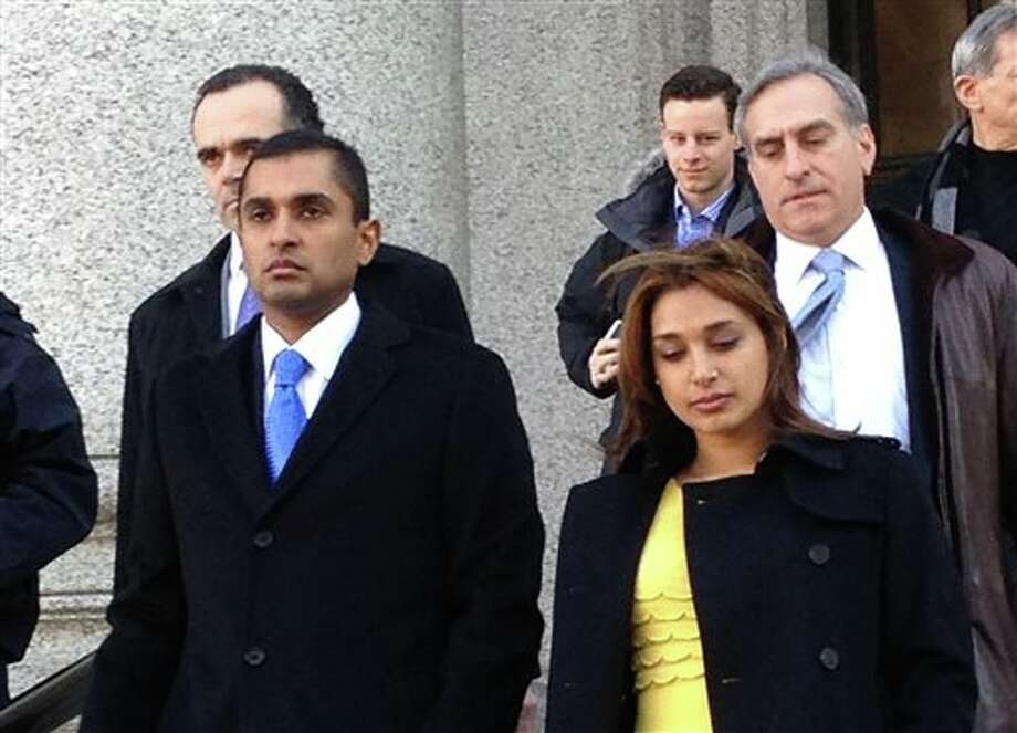 Mathew Martoma, left, leaves federal court in New York City with his wife, Rosemary, Thursday, Feb. 6, 2014, after being convicted of helping his company earn more than a quarter billion dollars illegally through trades based on secrets about the testing of a potential breakthrough Alzheimer's drug. The verdict capped a three-week trial that featured testimony from two prominent doctors who confessed spilling secrets to Mathew Martoma during lucrative consultations with financiers. (AP Photo/Larry Neumeister) Photo: Larry Neumeister / AP