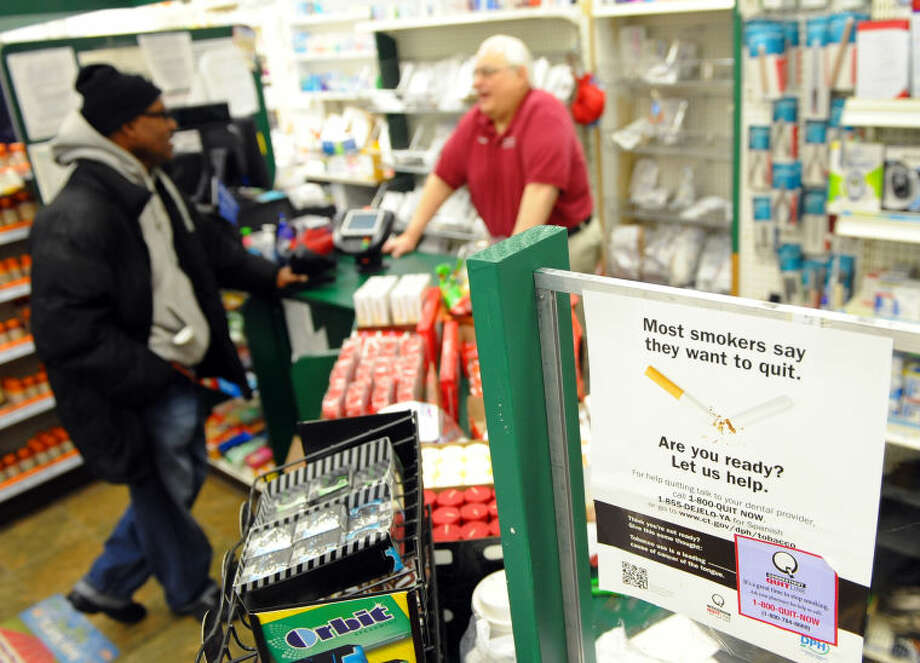 Dan Lupariello, owner of Lupe's Pharmacy helps customer Rodney Bowens, left, at the pharmacy on Main Street in Bridgeport, Conn. on Wednesday February 5, 2014. CVS has announced it will no longer sell cigarettes at any of its stores. Lupariello hasn't sold cigarettes at the store for 15 years. Photo: Christian Abraham