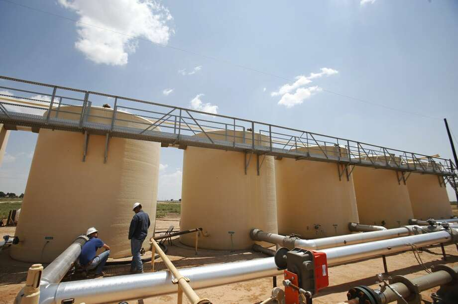 Pipeline technician Jeremy Wagner talks with gang pusher Ruben Duran next to the holding tanks of used drilling water on land owned by Fasken Oil and Ranch near Midland, Texas, on Wednesday, July 23, 2014. Water Rescue Services treats the water to recycle it for reuse for Fasken Oil and Ranch. (Vernon Bryant/Dallas Morning News/MCT) Photo: Vernon Bryant