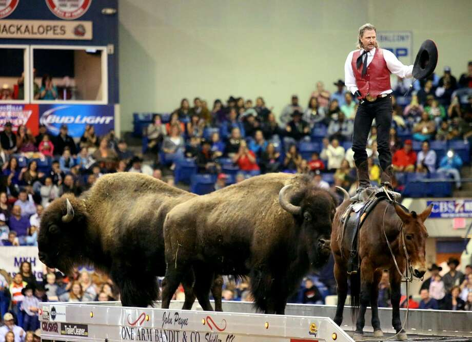 John Payne, the One Arm Bandit, stands on a mule after hearding two buffalo on top of a trailer during an intermission act on the second night of the Sandhills Stock Show and Rodeo Saturday Jan. 4, 2014 at the Ector County Coliseum in Odessa, Texas. (AP Photo/Odessa American, Edyta Blaszczyk) Photo: Edyta Blaszczyk | Odessa America