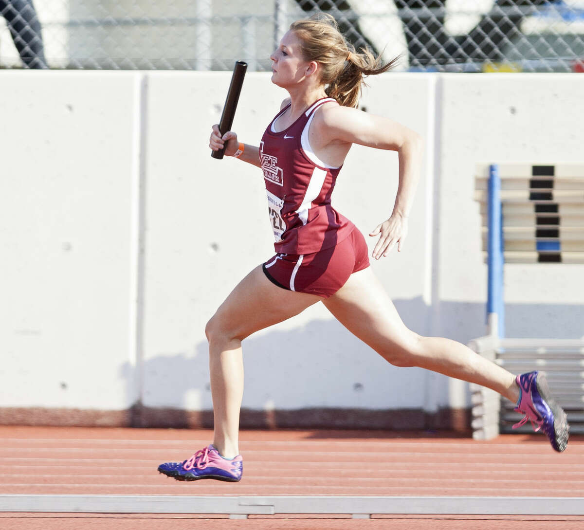 Midland Lee freshman Chelsea Adams carries the baton in the first leg of the 800 relay during the UIL Region I-6A Track and Field Championship on Friday at Maverick Stadium in Arlington.