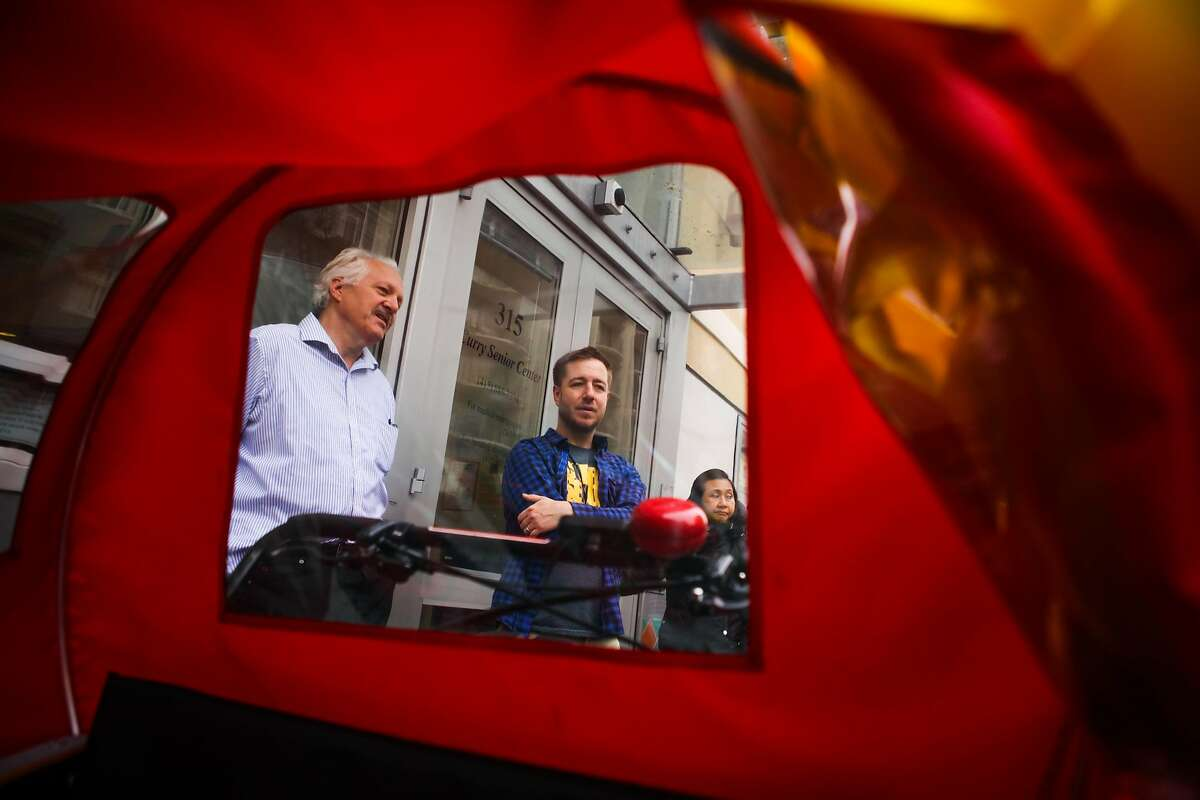 (l-r) David M. Knego and Arlo Buschnell, of the Curry Senior Center, are seen through a tricycle rickshaw, which was donated to the Curry Senior Center by Zendesk, in San Francisco, California, on Friday, May 6, 2016.