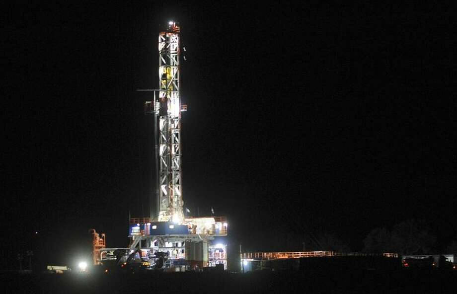 A hydraulic fracturing drilling rig shines in the night near Three Rivers, Texas, on Thursday, Dec. 13, 2012. Photo: Billy Calzada