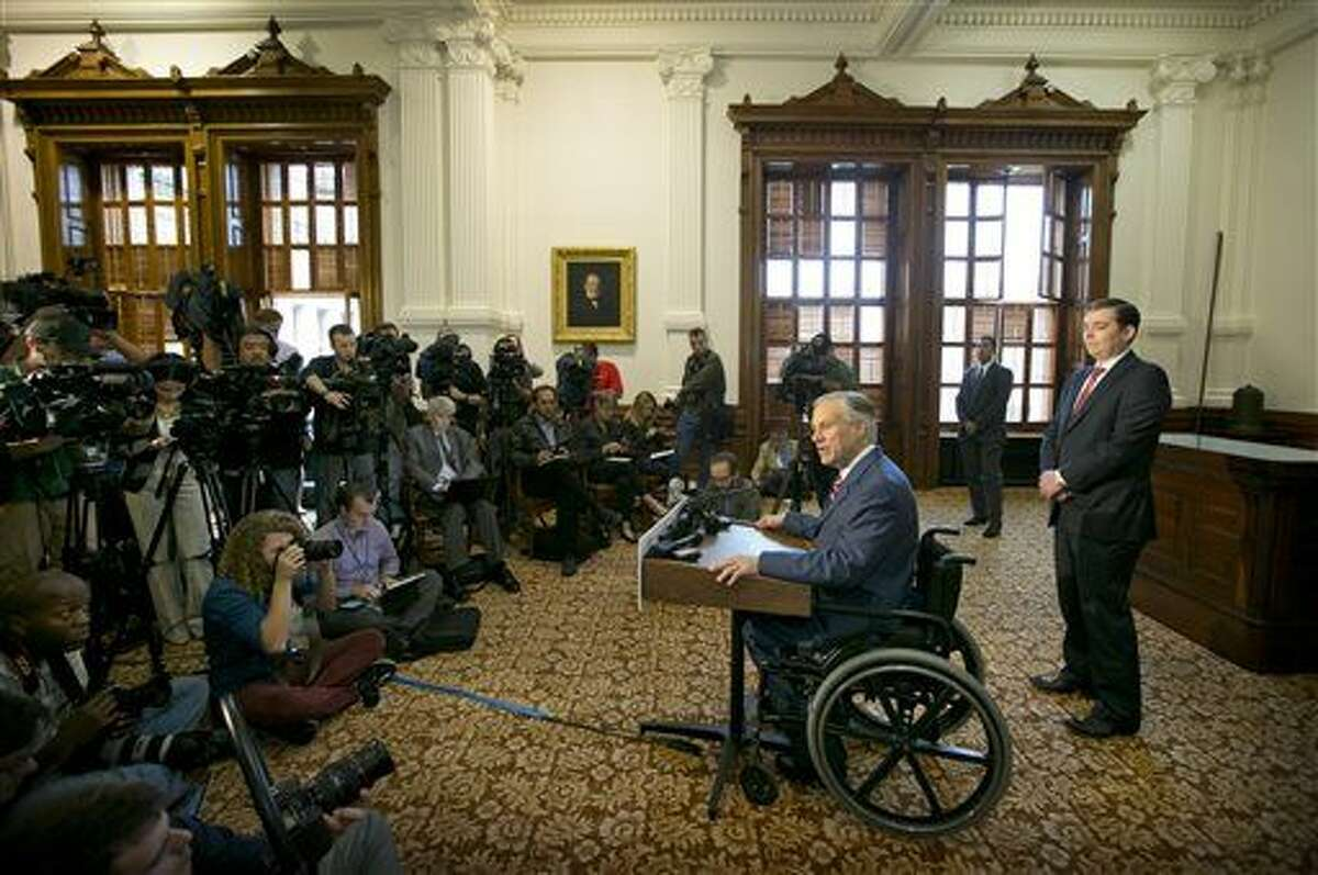 Texas Governor-elect Greg Abbott, center, addresses media, Wednesday, Nov. 5, 2014, at the Capitol in Austin, Texas. Abbott is the first new Texas governor in 14 years - and he did it in a landslide. He crushed Democrat Wendy Davis by one of the biggest margins in any of three dozen gubernatorial races across the U.S., carrying nearly 60 percent of the vote by early Wednesday as Texas underwent its biggest political shake-up in decades.