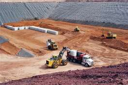 FILE - In this Oct. 14, 2009, photo provided by Waste Control Specialists, canisters filled with uranium byproduct waste are placed into a burial pit at at Waste Control Specialists near Andrews, Texas. People living nearest to the site would be barred from challenging license amendments sought by the company operating the facility under a Senate bill that could be voted on as early as Wednesday, April 17, 2013. The bill also encourages compact members Texas and Vermont to send their low-level waste elsewhere and seeks to prohibit public hearings or comment on some amendments to the company's license. (AP Photo/Waste Control Specialists, File)