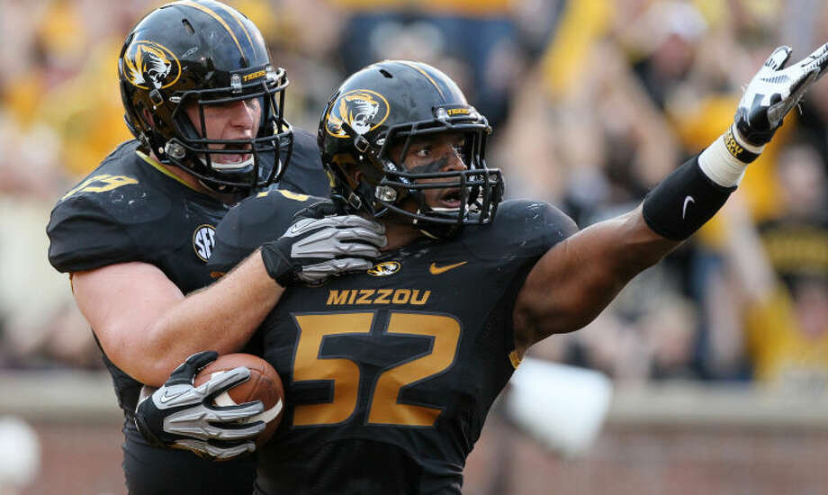 FILE - In this Sept. 1, 2012, file photo, Missouri linebacker Michael Sam (52) is congratulated by teammate Matt Hoch after returning a fumble seven yards for a touchdown against Southeastern Louisiana during the first quarter, in Columbia, Mo. Michael Sam hopes his ability is all that matters, not his sexual orientation. Missouri's All-America defensive end came out to the entire country Sunday night, Feb. 9, 2014, and could become the first openly gay player in America's most popular sport. (AP Photo/Chris Lee, St. Louis Post-Dispatch, File) Photo: Chris Lee