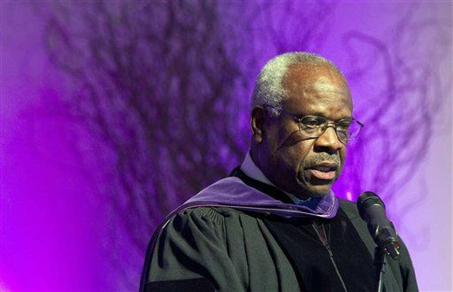 FILE - In this Jan. 26, 2012 file photo, Supreme Court Justice Clarence Thomas speaks at College of the Holy Cross in Worcester, Mass. Thomas has asked questions during Supreme Court arguments for the first time in 10 years. Thomas' question came Monday, Feb. 29, 2016, in a case in which the court is considering placing new limits on the reach of a federal law that bans people convicted of domestic violence from owning guns. (AP Photo/Michael Dwyer, File) Photo: Michael Dwyer