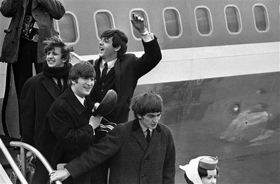 FILE - Britain's Beatles make a windswept arrival in New York in this Feb. 7, 1964 file photo, as they step down from the plane that brought them from London, at Kennedy airport. From left to right, Ringo Starr, John Lennon, Paul McCartney and George Harrison. One of the most tumultuous welcomes in pop history is to be recreated next month when UK officials and a tribute band recreate the Beatles' historic 1964 landing at JFK airport, in a bid to spark interest in Beatles-related tourism to Britain. (AP Photo, File) Photo: Uncredited / A1964
