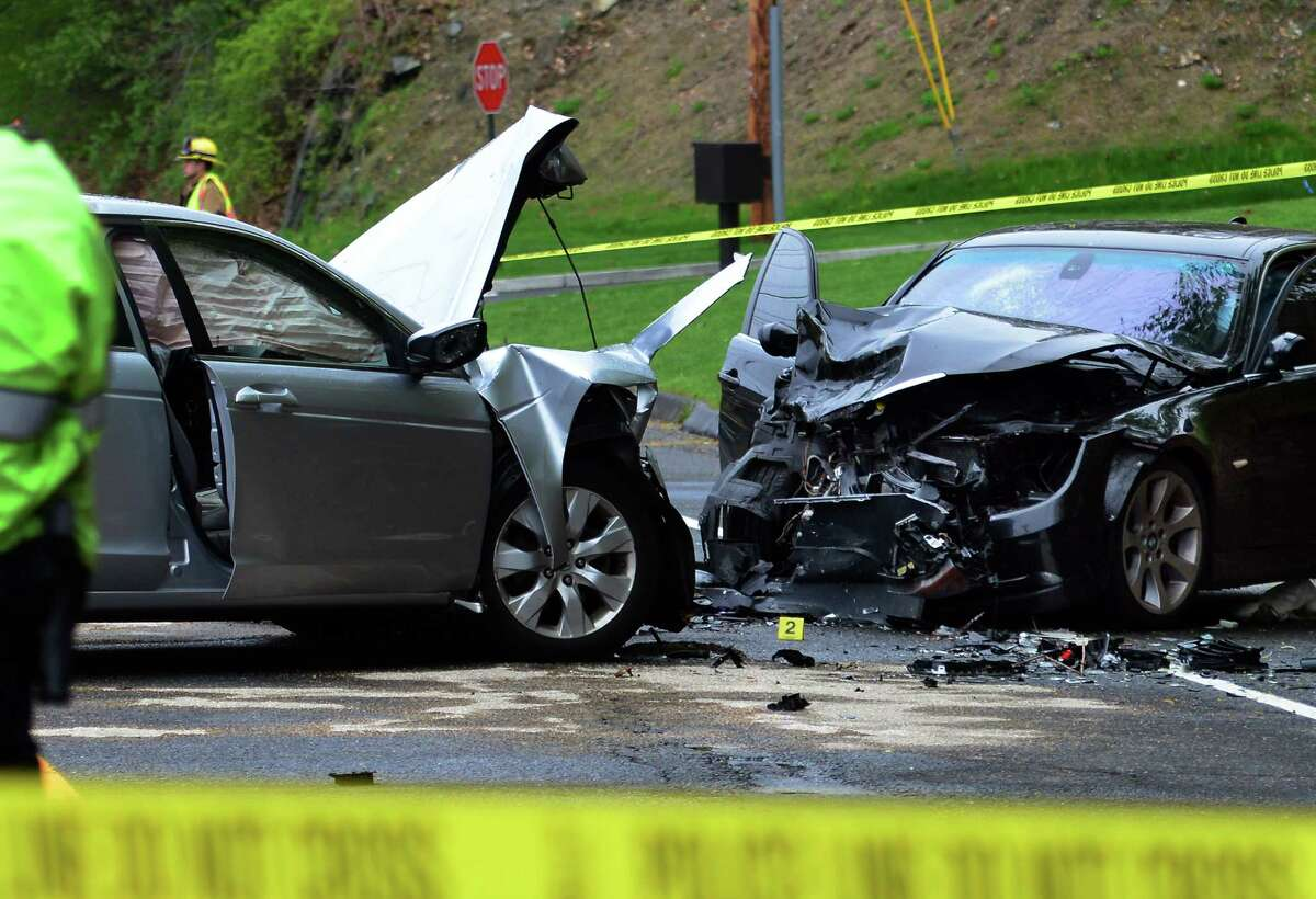 Police investigate at the scene of a head-on crash near the entrance to the Sports Center of Connecticut along Route 110 (River Road) in Shelton, Conn., on Friday May 6, 2016.