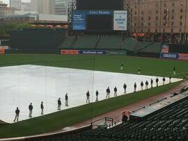 The grounds crew at Camden Yards prepares to remove water from the tarp before Friday's game between the Orioles and A's.
