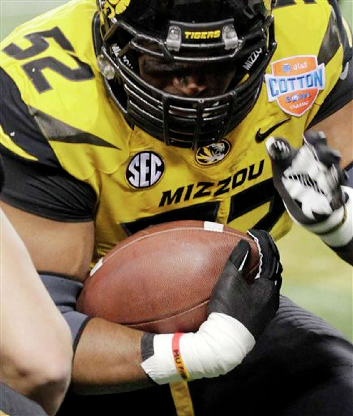 """In this Jan. 3, 2014 photo, Missouri defensive lineman Michael Sam (52) warms up, as he wears an """"MU Pride"""" bracelet made by Triangle Coalition, a student organization for lesbian, gay, bisexual and transgender people, before the Cotton Bowl NCAA college football game against Oklahoma State, in Arlington, Texas. Michael Sam hopes his ability is all that matters, not his sexual orientation. Missouri's All-America defensive end came out to the entire country Sunday night, Feb. 9, 2014, and could become the first openly gay player in America's most popular sport. (AP Photo/Tim Sharp)"""