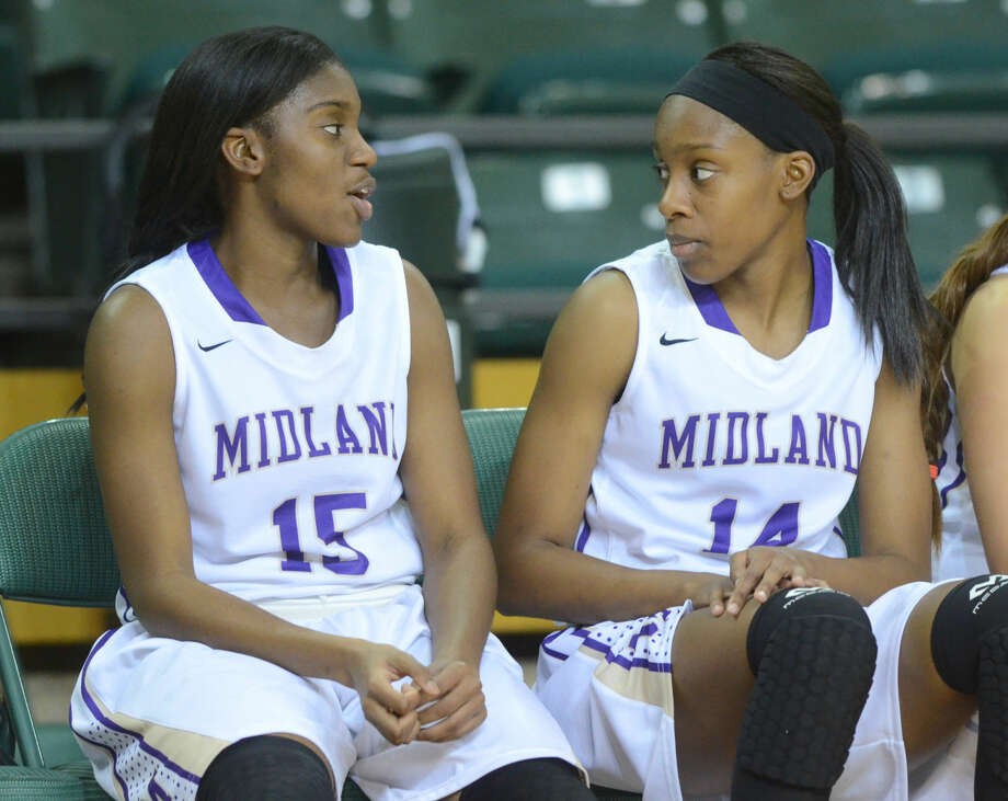 Midland High's Alexandrea Washington (left) and Alexis Washington (right) talk on the bench during the game against Odessa High on Tuesday, Jan. 12, 2016, at Chaparral Center. James Durbin/Reporter-Telegram Photo: James Durbin