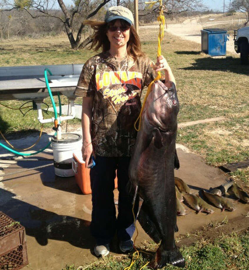 Midlander Kathy Kirby poses with the catfish that she caught Feb. 13 at O.H. Ivie Reservoir. Her husband, Dennis, grabs the 67 1/2-pound blue catfish. Photo: Courtesy Photo
