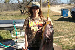 Midlander Kathy Kirby poses with the catfish that she caught Feb. 13 at O.H. Ivie Reservoir. Her husband, Dennis, grabs the 67 1/2-pound blue catfish.