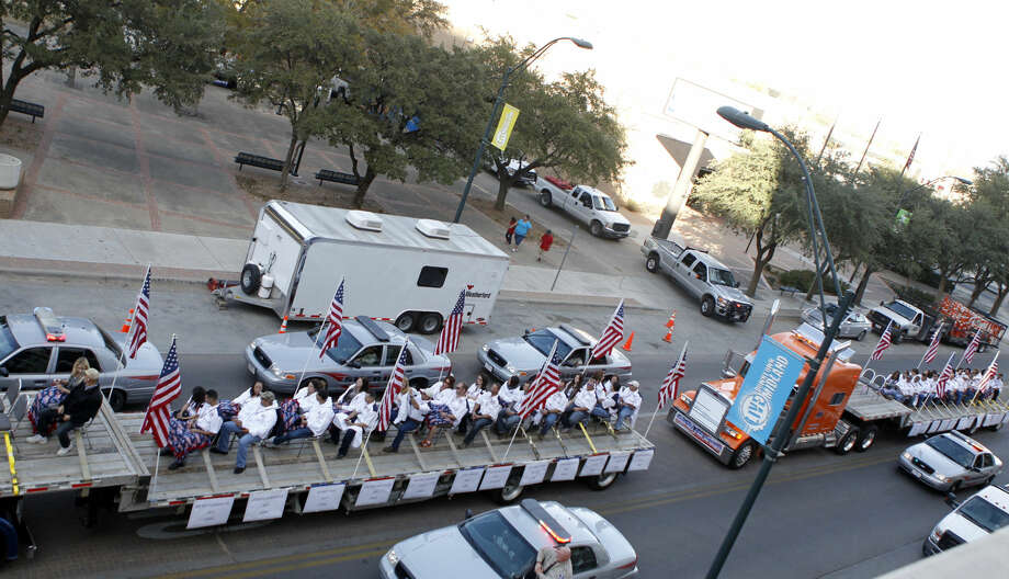 PREVIOUSLY UNRELEASED FILE PHOTO / Flatbed trucks carrying wounded veterans and their families drive down Wall Street during the Show of Support parade Nov. 15 in Midland. The flatbed truck on the far right of the image was struck by a train at a crossing on Garfield St., killing four and injuring 14. James Durbin/Reporter-Telegram Photo: JAMES DURBIN