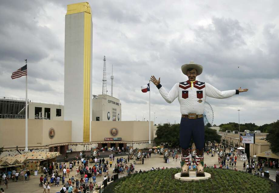 The Tower Building and the Cotton Bowl Stadium can be seen behind visitors to the fair ground as they walk around after an official ceremony welcoming back Big Tex, Friday, Sept. 27, 2013, in Dallas. This year is the 61st year that the structure has welcomed visitors to the fair. (AP Photo/Tony Gutierrez) Photo: Tony Gutierrez