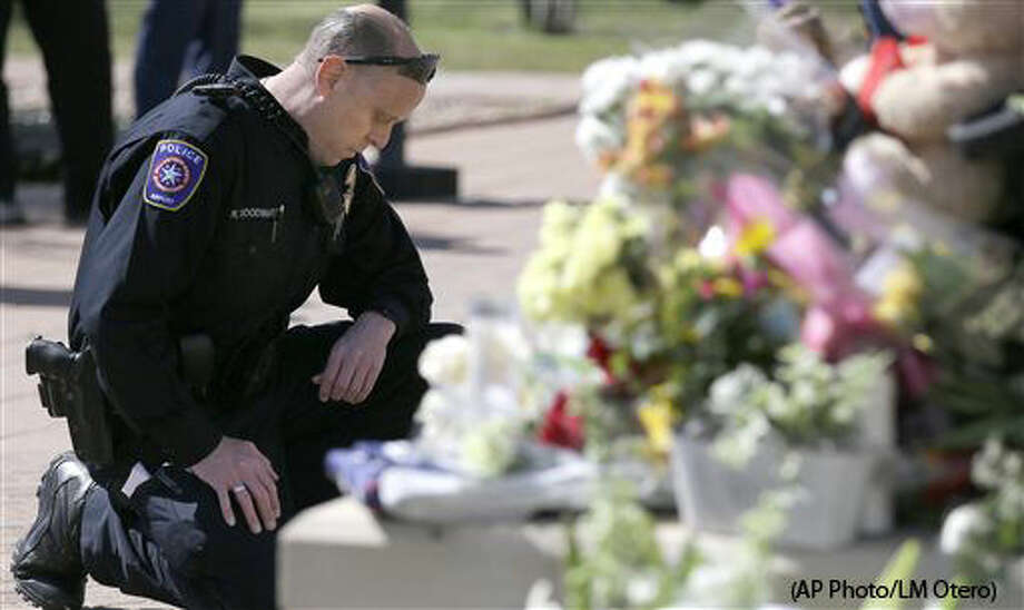 DFW Airport Police officer Robert Woodward kneels in front of a makeshift memorial for a slain officer at the Euless Police Department Wednesday, March 2, 2016, in Euless, Texas. Officer David Hofer died after he was shot in a Tuesday afternoon gunfight with an armed suspect in a park near a Dallas-area school, police said. Hofer, who previously worked for the New York Police Department, died during surgery. The suspect was also killed. (AP Photo/LM Otero) Photo: LM Otero