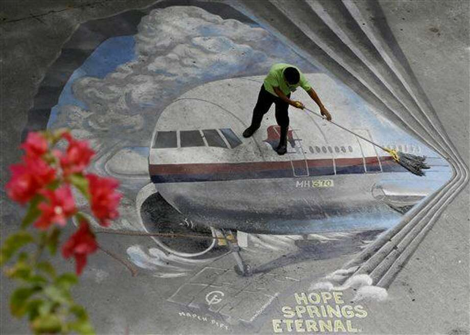 "FILE - In this April 8, 2014, file photo a school utility worker mops a mural depicting the missing Malaysia Airlines Flight 370 at the Benigno ""Ninoy"" Aquino High School campus at Makati city east of Manila, Philippines. A U.S. official says debris washed up over the weekend in Mozambique has been tentatively identified by experts close to the investigation as a part from the tail of the same type of aircraft as the missing Malaysia Airlines Flight 370. (AP Photo/Bullit Marquez, File) Photo: Bullit Marquez"