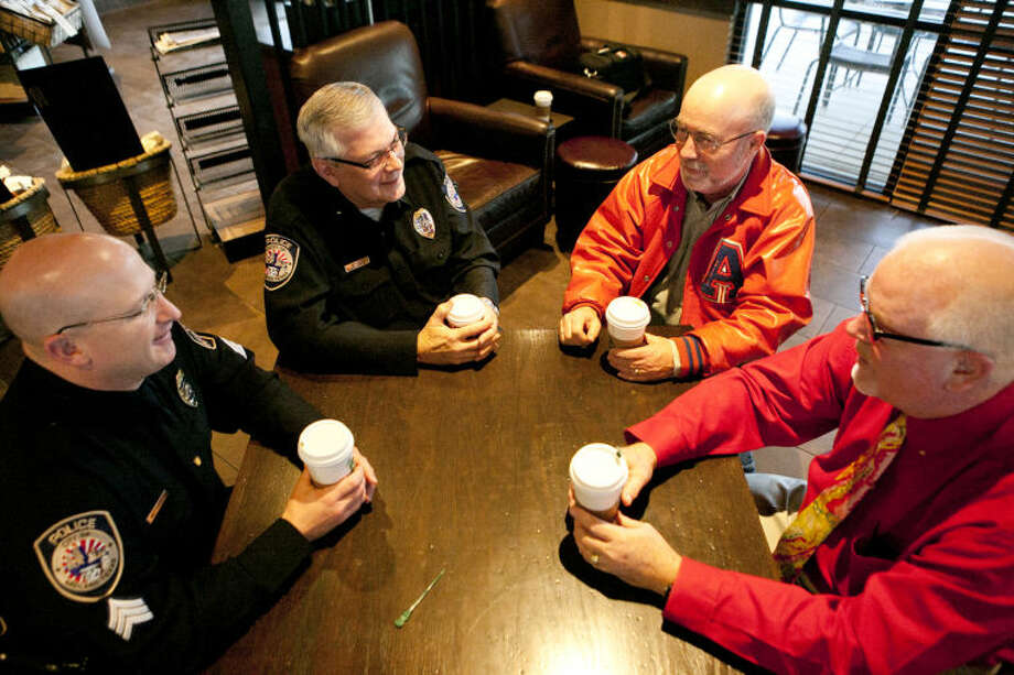 """Clockwise from left, Midland Police officers Craig Matthews and J.R. Smith talk with Joe Willis and Midland County District Clerk Ross Bush during a """"Coffee with Cops"""" event at the Starbucks on Midland Drive on Wednesday. James Durbin/Reporter-Telegram Photo: JAMES DURBIN"""