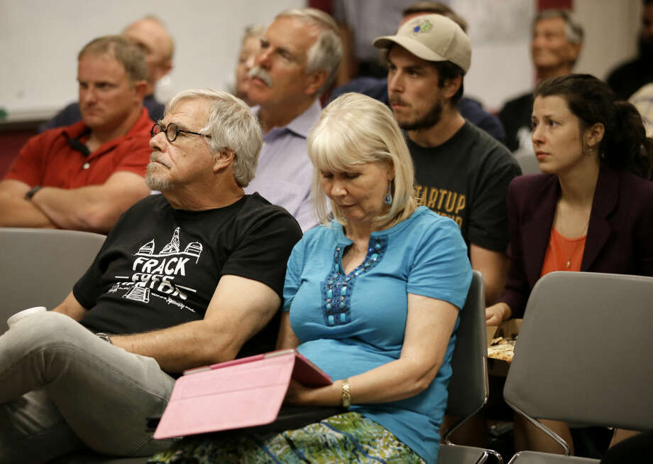 Area residents and registered speakers watch proceedings on a television screen from one of the three overflow rooms as others wait their turn to address the city council during a public hearing, Tuesday, July 15, 2014, in Denton, Texas. The North Texas city could become the first in the state to ban hydraulic fracturing if city leaders approve a citizen-led petition to outlaw the drilling method. (AP Photo/Tony Gutierrez) Photo: Tony Gutierrez