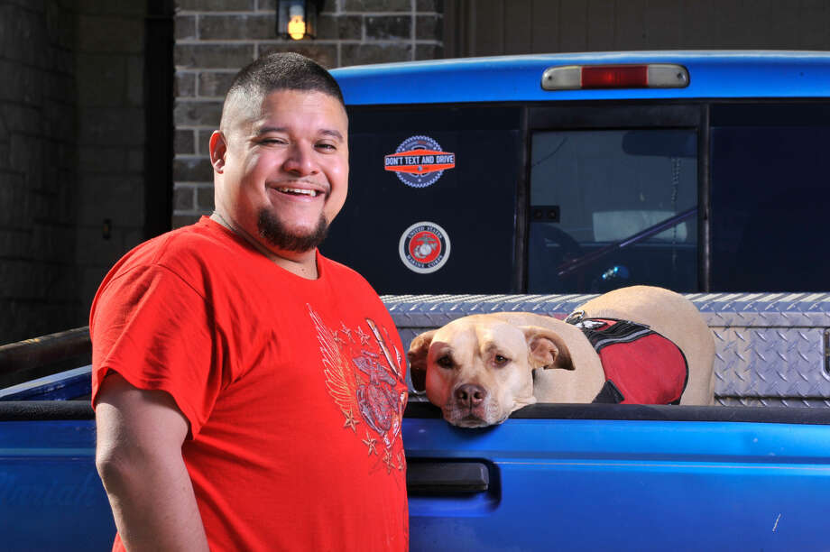 Juan Alonzo-Miranda and his service dog Goldie walk near their far west side home. Alonzo-Miranda sued Schlumberger Technologies Corp. alleging it violated the Americans with Disabilities Act by not allowing Goldie at his job to help him cope with Post Traumatic Stress Disorder. Photo: Robin Jerstad
