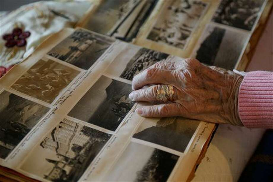 "In this March 1, 2016 photo, Amelia Greeley looks over old photos taken in the South Pacific during World War II as she reflects on her time spent as an Army nurse in New York. Greeley, who goes by Mimi, celebrated her 100th birthday this week and will be sharing the milestone this year with a friend, Ruth ""Brownie"" Girk, she made nearly 70 years ago during the war. (AP Photo/Julie Jacobson) Photo: Julie Jacobson"