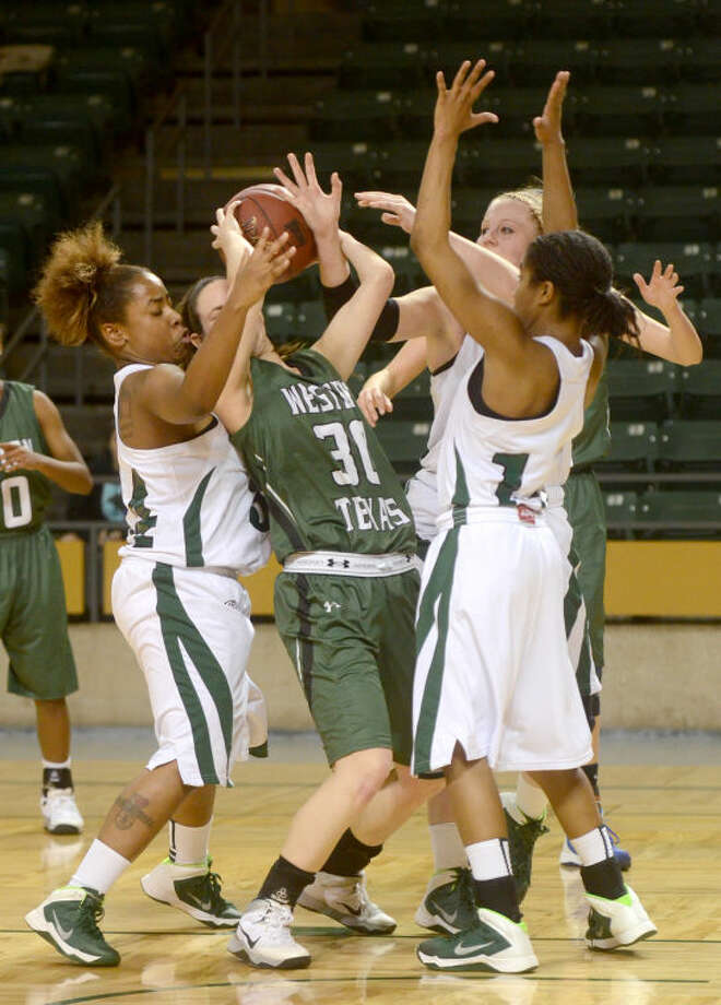 Midland College's Ashleigh Sparks (34), Catherine Kruschke (24) and Tajanay Veiga (10) take a rebound away from Western Texas' Brittany McPherson (30) on Thursday at Chaparral Center. James Durbin/Reporter-Telegram Photo: JAMES DURBIN