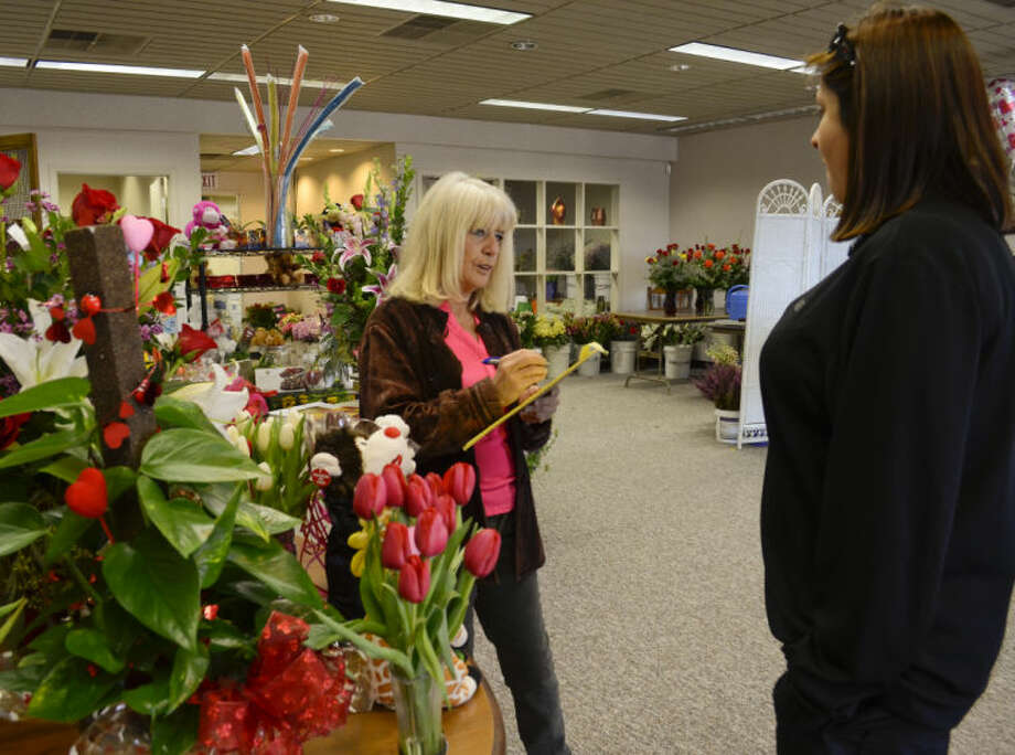 Jan Lawbaugh, owner of Fine Flowers and Scents, takes a Valentine's Day order from Cindy Carrasco Thursday morning at the shop. Tim Fischer\Reporter-Telegram Photo: Tim Fischer