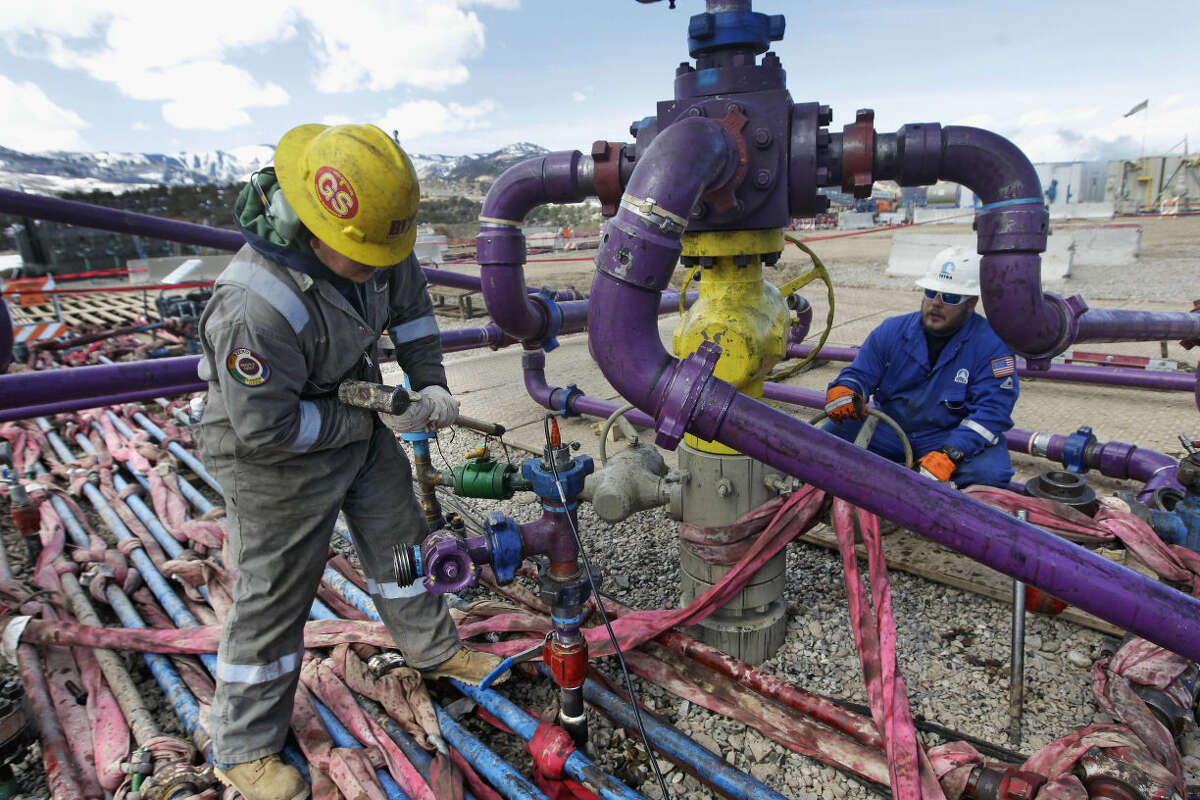 In this March 29, 2013, file photo, workers tend to a well head during a hydraulic fracturing operation at an Encana Oil & Gas (USA) Inc. gas well outside Rifle, Colo.